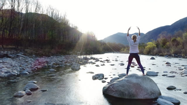 vídeos de stock, filmes e b-roll de mulher praticando ioga pelo rio, tiro do zangão - braço humano