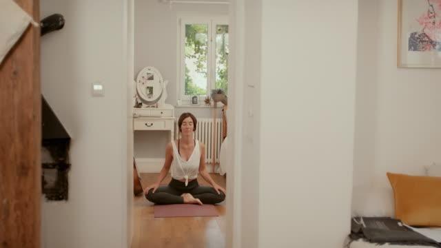 vidéos et rushes de woman practicing yoga in bedroom at home - femmes d'âge moyen