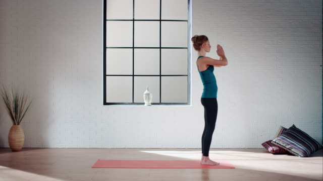 woman practicing yoga in gym (sun salutation) - sun salutation stock videos and b-roll footage