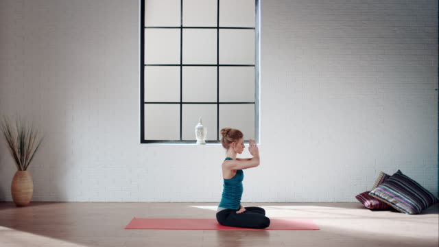 woman practicing yoga in gym (lotus pose) - pilates stock videos and b-roll footage
