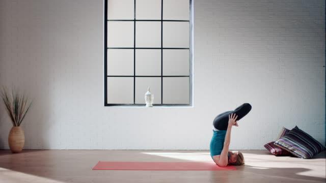 praticare yoga donna in palestra (la spalla stand in lotus - gambe incrociate video stock e b–roll