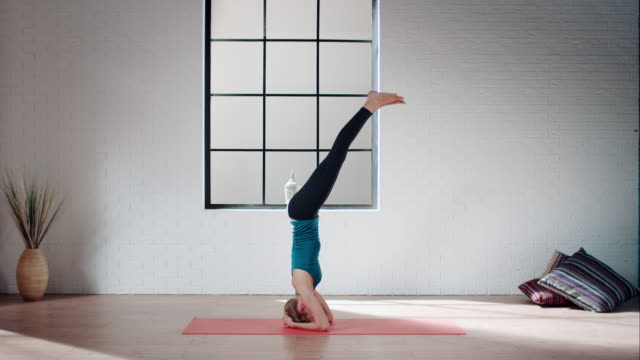 Woman practicing yoga in gym (headstand pose)
