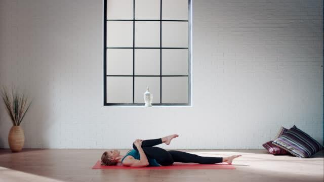 frau üben yoga im fitnessraum (dehnung bein am rücken - turnen stock-videos und b-roll-filmmaterial