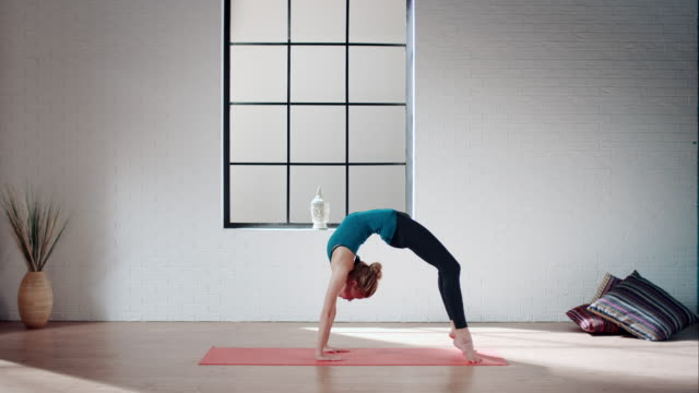 Woman practicing yoga in gym (bridge pose variation)