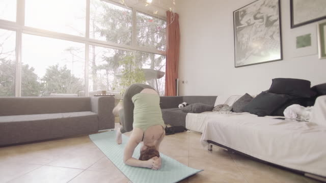woman practicing yoga in living room - early morning exercise stock videos & royalty-free footage