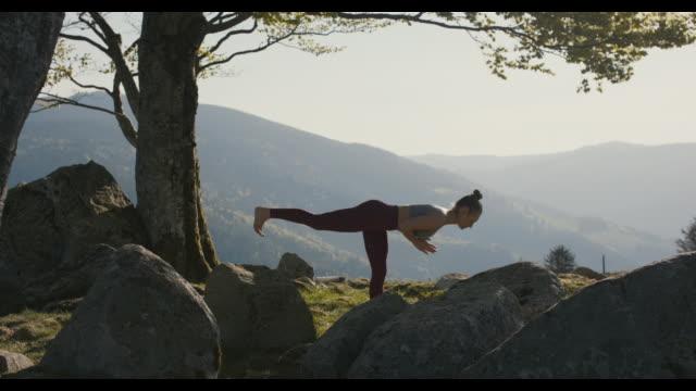 vídeos de stock, filmes e b-roll de woman practicing yoga in nature - equilíbrio