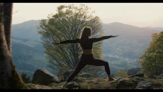 woman practicing yoga in nature - serene people stock videos & royalty-free footage