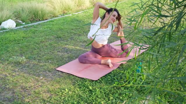 stockvideo's en b-roll-footage met woman practicing yoga in public park - in kleermakerszit