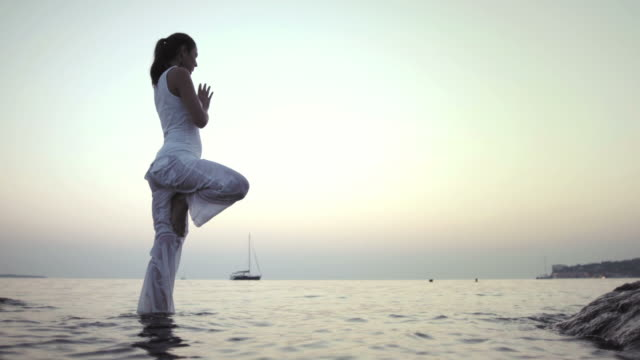 hd: woman practicing yoga in the sea - on one leg stock videos & royalty-free footage
