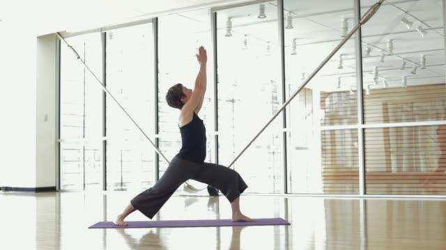 ws woman practicing yoga in yoga studio / vancouver, british columbia, canada - solo una donna di età media video stock e b–roll