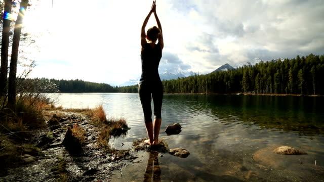 vídeos de stock, filmes e b-roll de mulher praticando yoga movimentos by the lake - pose de arvore