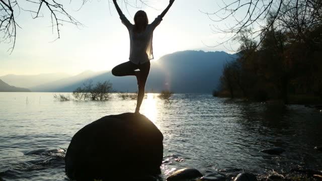 Woman practicing yoga near lake at sunset