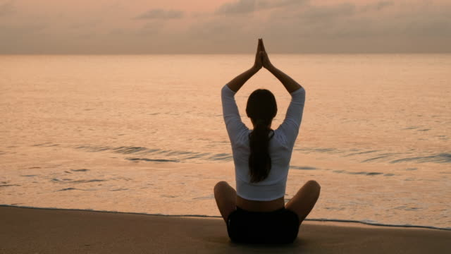 woman practicing yoga on beach - 後ろで束ねた髪点の映像素材/bロール