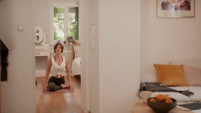 woman practicing yoga on bedroom floor - stretching stock videos & royalty-free footage
