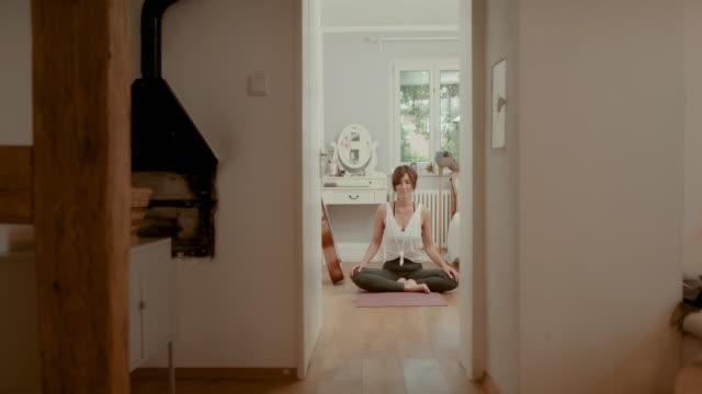 woman practicing yoga on bedroom floor - lotus position stock videos & royalty-free footage