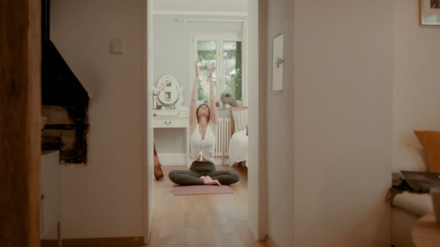 woman practicing yoga on bedroom floor - cross legged stock videos & royalty-free footage