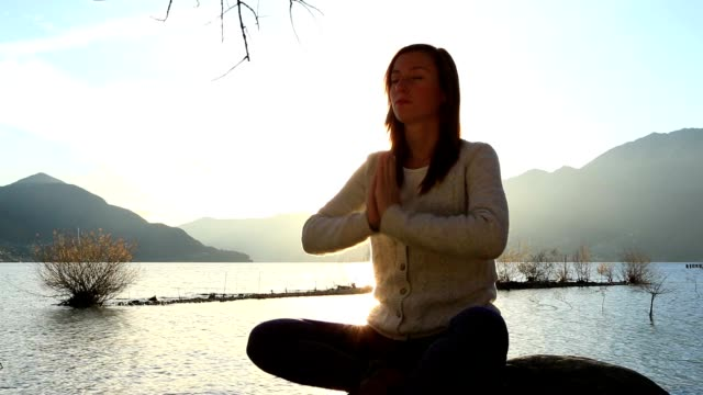 frau üben yoga auf felsen in der nähe von lake - gelassene person stock-videos und b-roll-filmmaterial