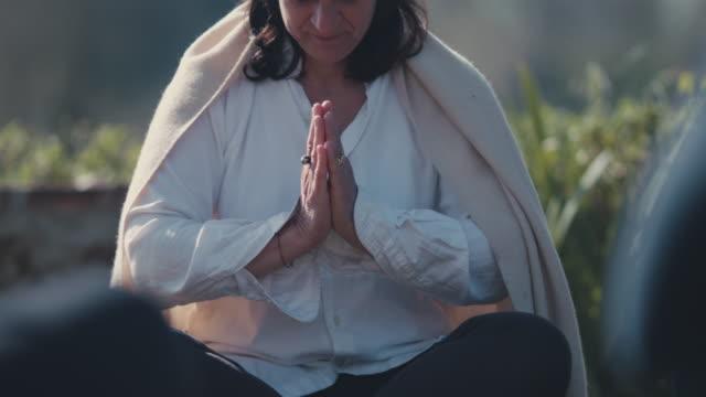 stockvideo's en b-roll-footage met woman practicing yoga outside - in kleermakerszit