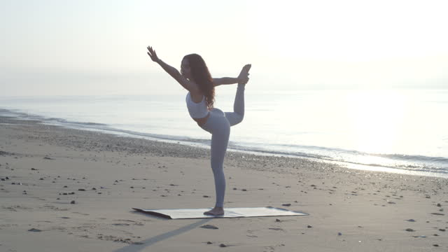 a woman practicing yoga standing bow pulling poses on a rocky beach at sunset, social distancing. - slow motion - solo ragazze video stock e b–roll