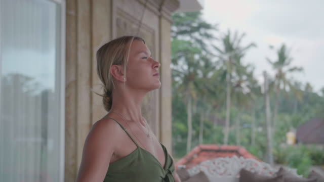 a woman practicing yoga standing prayer posture pose at a resort hotel spa. - gratitude stock videos & royalty-free footage