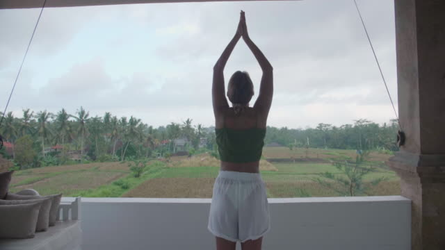 a woman practicing yoga standing prayer posture pose at a resort hotel spa. - posture stock videos & royalty-free footage