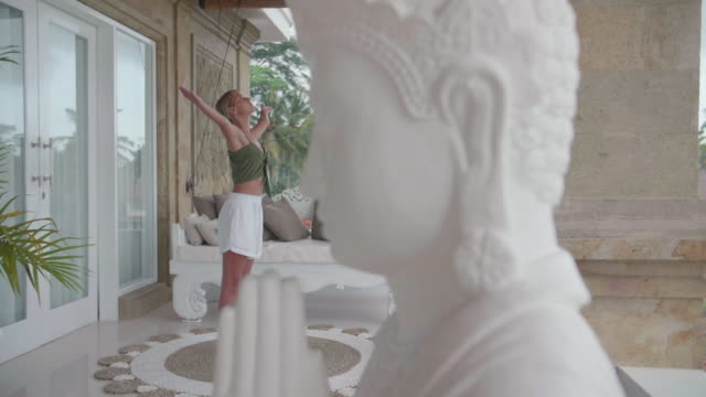 a woman practicing yoga standing prayer posture pose at a resort hotel spa with a buddha statue. - ubud district stock videos & royalty-free footage