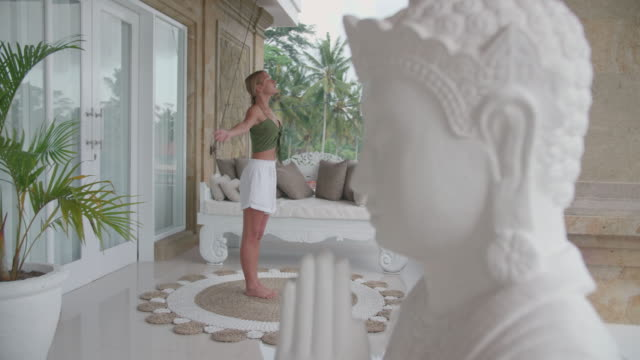 a woman practicing yoga standing prayer posture pose at a resort hotel spa with a buddha statue. - posture stock videos & royalty-free footage
