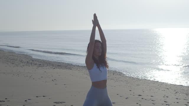 vídeos y material grabado en eventos de stock de a woman practicing yoga tree prayer poses on a beach at sunset, social distancing. - slow motion - vriksha asana