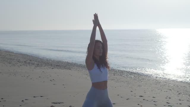 vídeos de stock, filmes e b-roll de a woman practicing yoga tree prayer poses on a rocky beach at sunset, social distancing. - pose de arvore