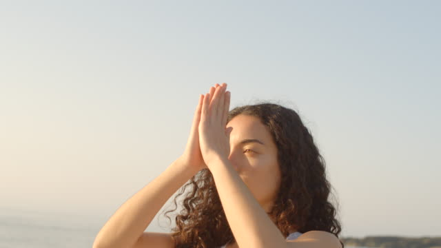vídeos y material grabado en eventos de stock de a woman practicing yoga tree prayer poses on a rocky beach at sunset, social distancing. - vriksha asana