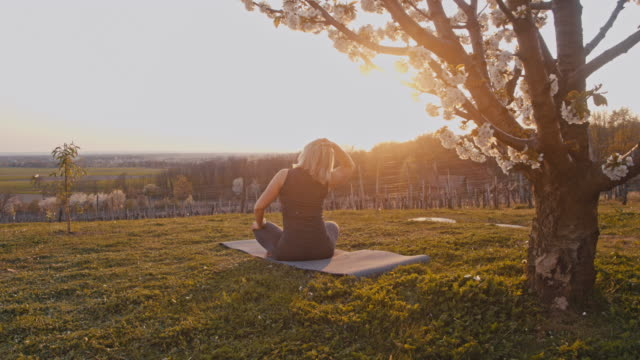 slo mo woman practicing yoga under a blooming cheery tree - posa del loto video stock e b–roll