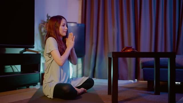 vidéos et rushes de femme pratiquant le yoga tout en regardant des tutoriels de yoga en ligne sur téléphone intelligent à la maison la nuit - assis en tailleur