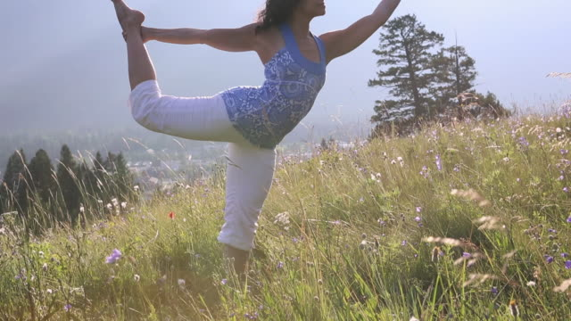 woman practises yoga moves in mountain meadow - auf einem bein stock-videos und b-roll-filmmaterial