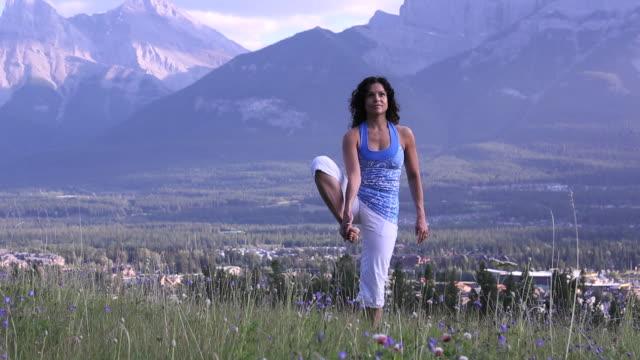 woman practises yoga moves, mountains behind - auf einem bein stock-videos und b-roll-filmmaterial