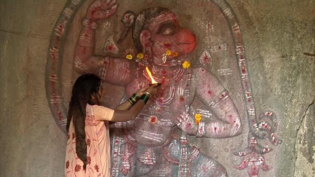MS, Woman praying at carving of Hanumana with flowers, Hampi, Karnataka, India