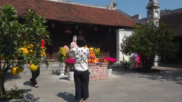 Woman praying at Ngoc Son Buddhist temple at Hanoi during Tet. Fruit religious offering
