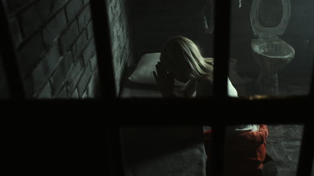 woman praying at prison cell - pregare video stock e b–roll