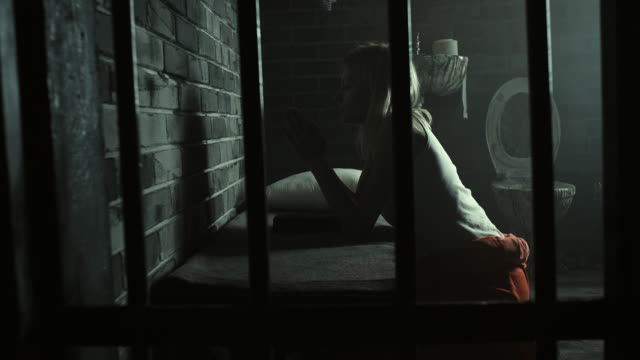 Woman praying at prison cell
