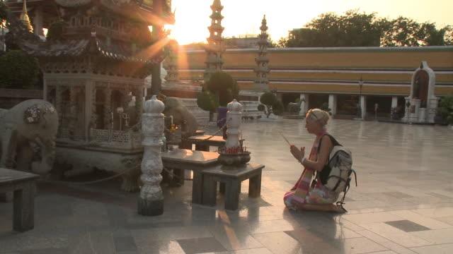 WS ZI Woman praying at Wat Phra Kaew (Temple of the Emerald Buddha), Bangkok, Thailand
