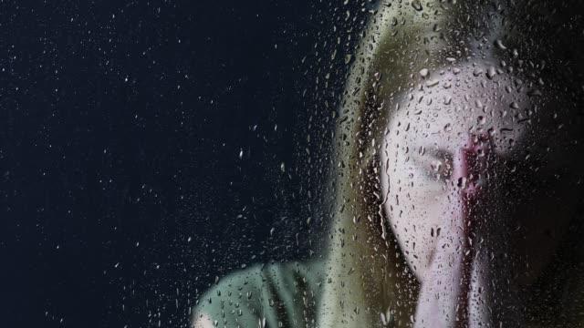 vídeos de stock e filmes b-roll de woman praying desperately by window on rainy day - condensação