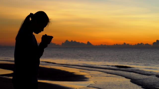 woman praying on beautiful sunset background - christianity stock videos & royalty-free footage