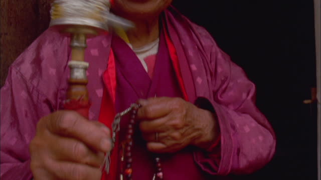 a woman prays, fingers her prayer beads and spins a mani wheel. available in hd. - prayer beads stock videos & royalty-free footage