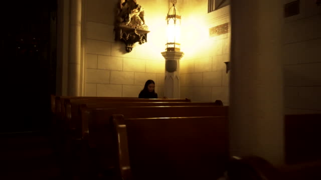woman prays in church pew, new mexico - catholicism stock videos & royalty-free footage