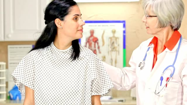 woman prepares for breast exam, mammogram at doctor's office or hospital. - gynecological examination stock videos and b-roll footage