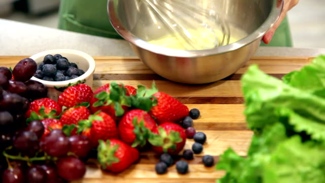 woman prepares fruit dessert in home kitchen. - mixing bowl stock videos and b-roll footage