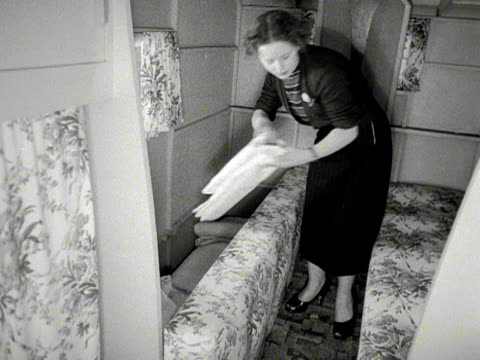 a woman prepares the beds in a small caravan then opens the ventilation window 1953 - bedclothes stock videos & royalty-free footage