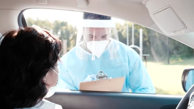 woman prepares to be tested at covid-19 drive through testing site - nurse waving stock videos & royalty-free footage