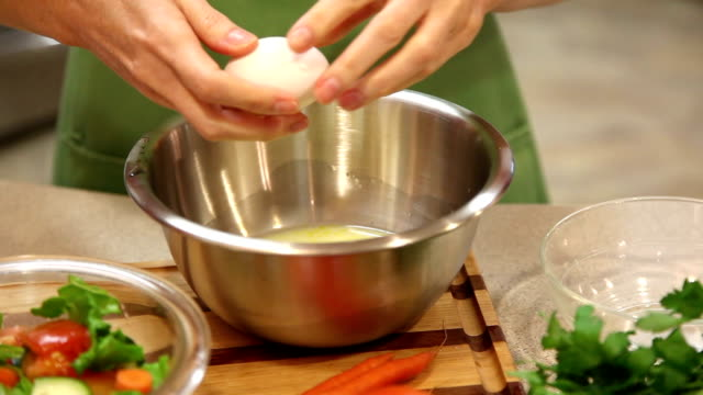 Woman prepares vegetable dish in home kitchen.
