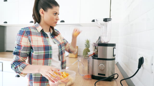 woman preparing a healthy smoothie. - electric juicer stock videos & royalty-free footage