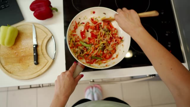 vídeos de stock e filmes b-roll de woman preparing a meal - cooking pan